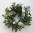 holiday decoration with mixed greenery, berries, ornaments