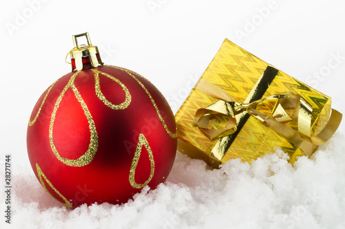 Christmas gift box and christmas ball on snow