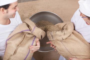 zwei bäcker schütten korn in die mühle