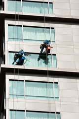 Two men cleaning windows on a high rise building