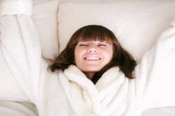 Woman falling backward onto bed