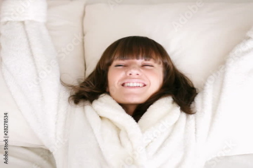 Woman falling backward onto bed