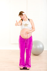 Pregnant woman with measure tape and showing thumbs up .