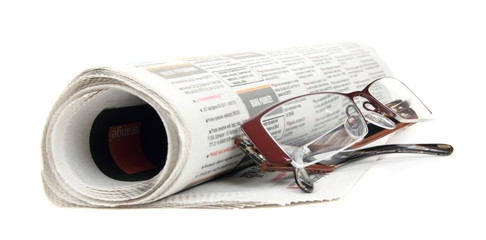 Roll of newspapers with eyeglasses