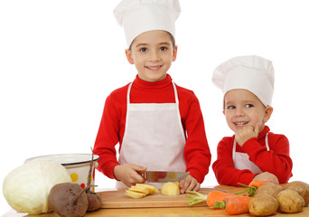 Smiling little chief-cookers on the desk with vegetables