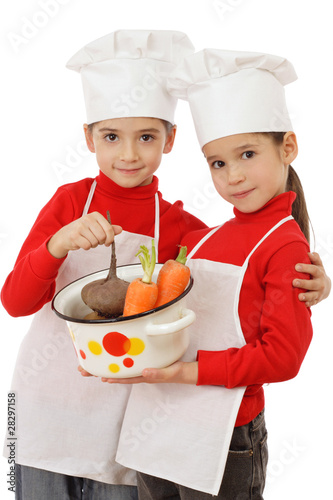 Two little chief-cookers holding a pot with vegetables