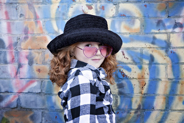 Red haired little girl in front of brick wall