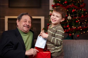Young boy giving christmas present to grandfather