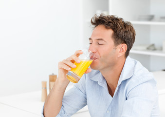 Handsome man enjoying his orange juice sitting in the kitchen