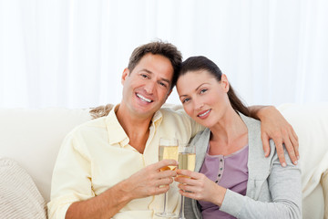 Portrait of a couple holding flutes of champagne on the sofa