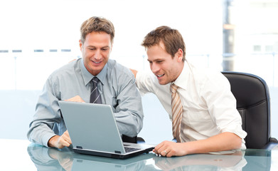 Two happy businessmen working together on a laptop sitting at a