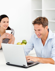 Lovely woman drinking coffee while her husband is working