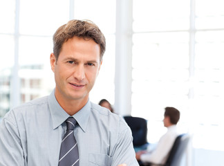 Severe businessman standing in front of his team while working a