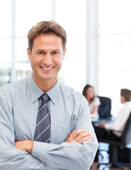 Happy businessman standing in front of his team while working at
