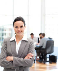 Cheerful businesswoman standing in front of her team while worki