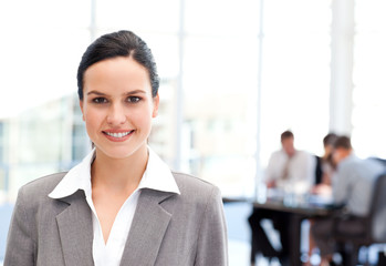 Adorable businesswoman standing in front of her team while worki