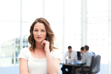 Pensive businesswoman standing in front of her team while workin