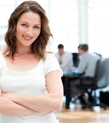 Happy businesswoman  posing in front of her team while working