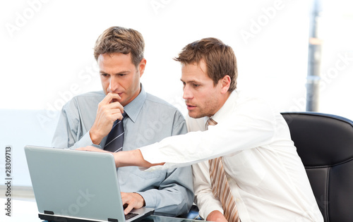Two handsome businessmen working together on a project sitting a