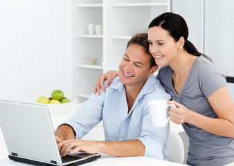 Affectionate woman looking at her boyfriend working on the lapto