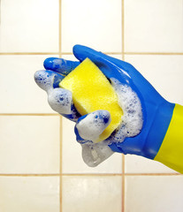 hand wearing a working glove and a sponge