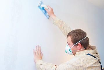 Young man builder polishing the wall. house environment theme.