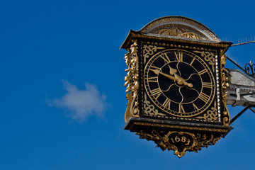 Clock over a blue sky with small cloud