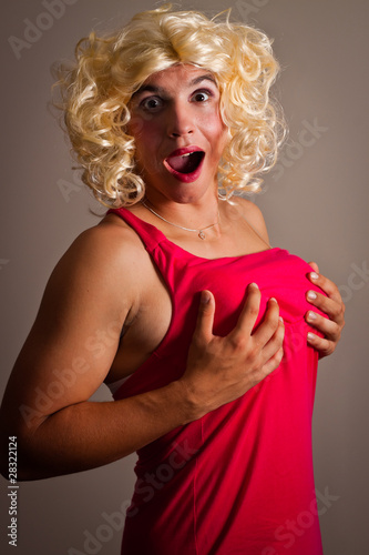 A man dressed as a woman holding his breasts