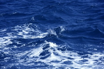Blue wawy water with white foam in storme sea ocean surface