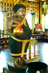 Fat buddha statue hold silver and gold bags