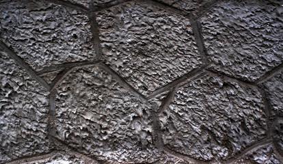 part of a stone gray cement wall fills the entire background