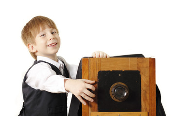 cheerful boy retro photographer with vintage camera in studio