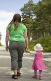 Obese mother and child walking on a forest path poster