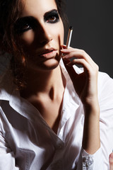 Fashion chic woman model smoking a cigarette. Rock make-up