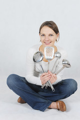 Smiling woman holding kitchen tools in the hands