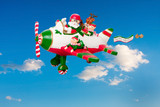 Flying Santa Claus with Elves in Airplane poster