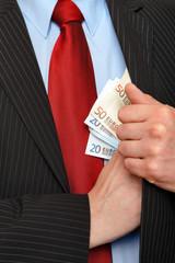 Mann steckt sich Geldscheine in die Innentasche seines Anzugs
