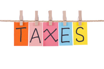 Taxes, Colorful words hang on rope by wooden peg