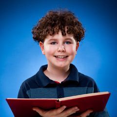 Boy reading book on blue background