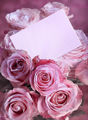 A bouquet of pink roses with a greeting card