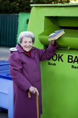 A senior woman recycling a book