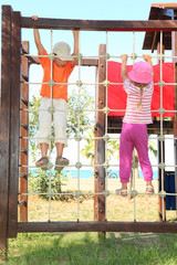 little boy and girl climbing on rope ladder at playground