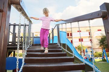 little girl standing on suspension bridge on playground