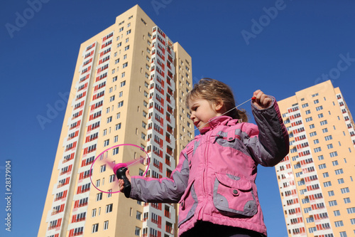 beautiful little girl in pink jacket, plays with propeller.