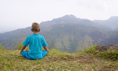 Photo of a boy meditating in mountain
