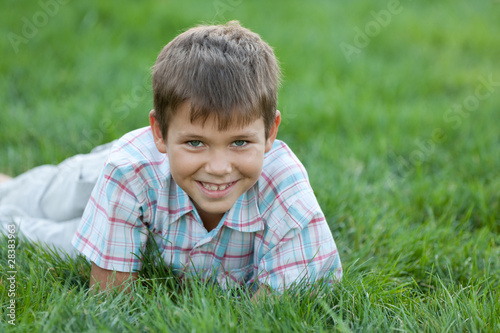 Smiling kid on the green grass
