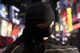 Thief wearing ski mask with city lights on the background
