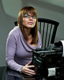 Beautiful young woman in glasses at a vintage typewriter