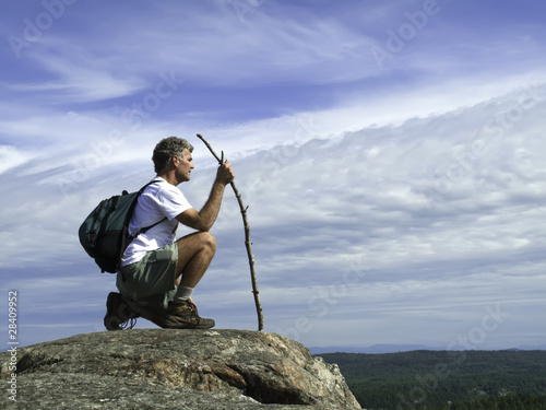 Man Kneeling On Wilderness Summit