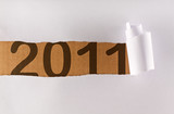 Torn wrapping paper revealing 2011 text - new year concept poster
